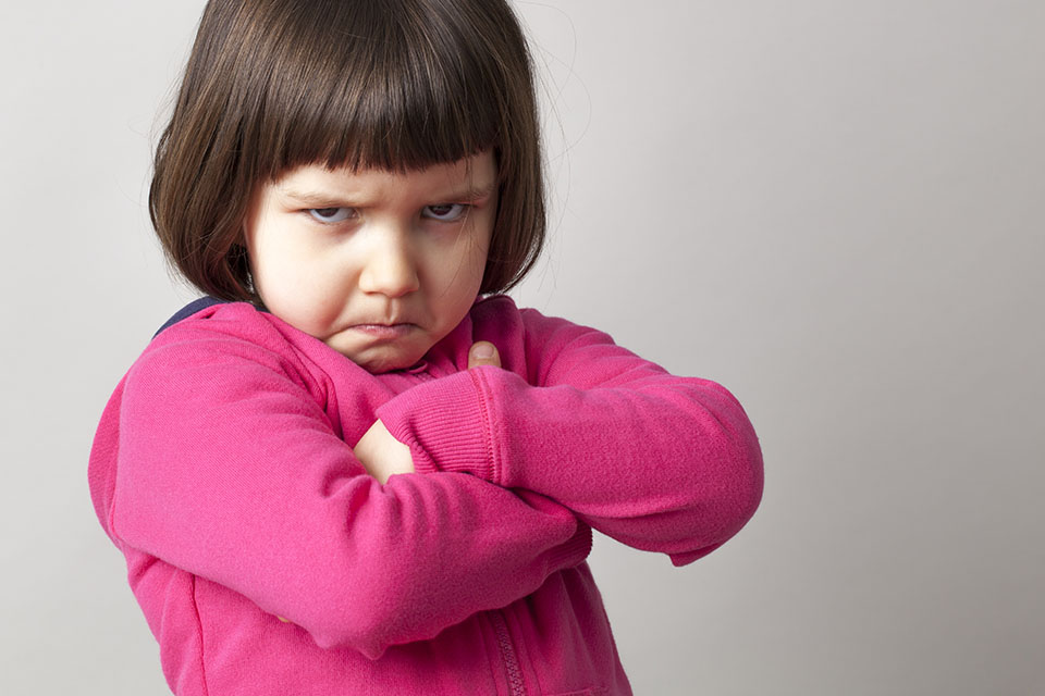 Frustrated Young Child Sulking With Crossed Arms And Dirty Look